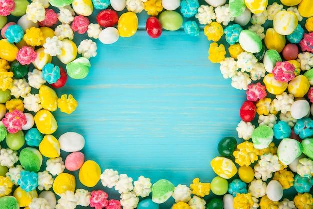 Vista superior de doces de açúcar doce colorido sobre fundo azul de madeira, com espaço de cópia