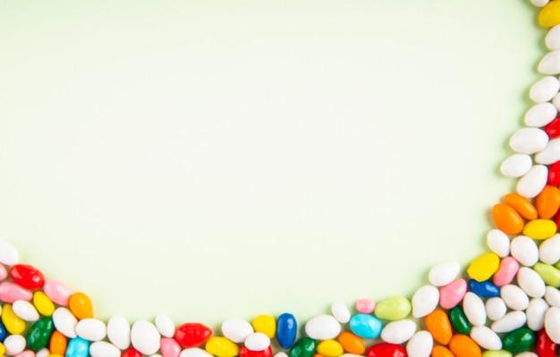 Vista superior de doces de açúcar doce colorido sobre fundo branco, com espaço de cópia