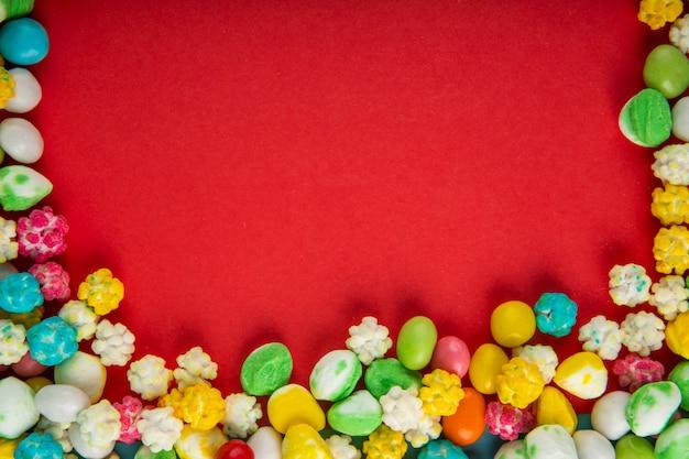 Vista superior de doces de açúcar doce colorido sobre fundo vermelho, com espaço de cópia