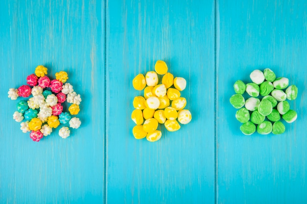 Vista superior de doces de açúcar duro de fruta colorida sobre fundo azul de madeira