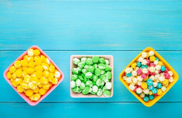 Vista superior de doces de açúcar duro de frutas coloridas em taças sobre fundo azul de madeira, com espaço de cópia