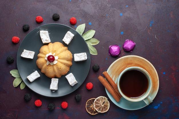 Vista superior de doces de açúcar em pó delicioso torrão com bolo e confiture chá de frutas vermelhas na superfície escura