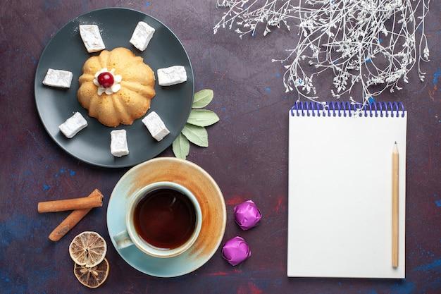 Vista superior de doces de açúcar em pó delicioso torrão com bolo e xícara de chá dentro do prato na superfície escura