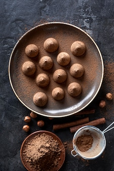 Vista superior de doces de chocolate com cacau em pó e paus de canela