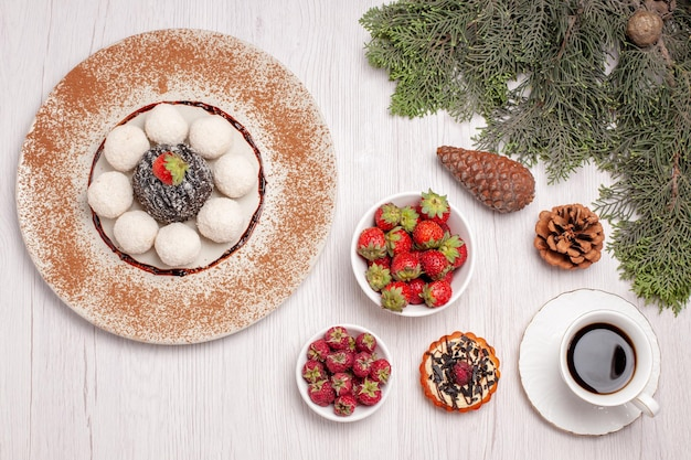 Vista superior de doces de coco saborosos com chá de bolo e frutas em branco