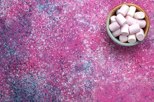Vista superior de doces deliciosos marshmallows dentro de uma panela redonda na superfície rosa