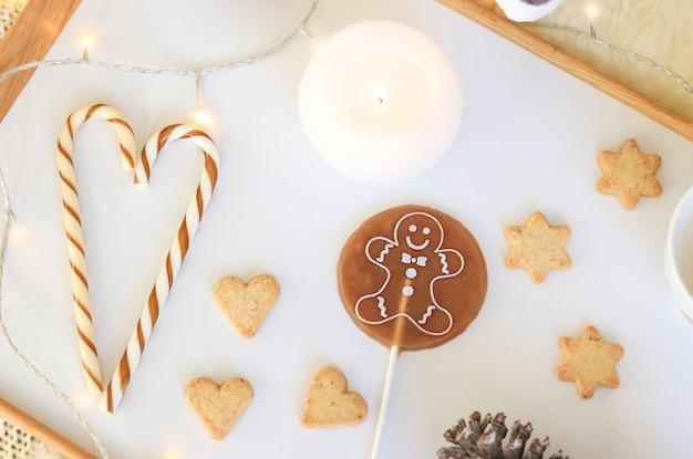 Vista superior de doces do natal na bandeja branca. bastão de doces, rodada pirulito de homem de gengibre
