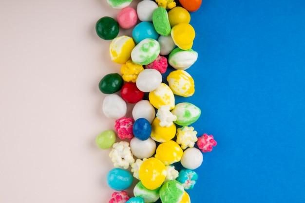 Vista superior de doces em esmalte multi-colorido sobre fundo azul e branco, com espaço de cópia