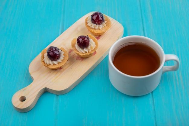 Vista superior de doces em uma placa de cozinha de madeira com uma xícara de chá em um fundo azul de madeira