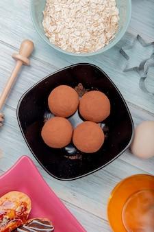 Vista superior de doces em uma tigela com flocos de aveia, manteiga, ovo na mesa de madeira