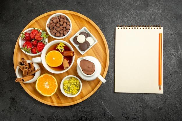 Vista superior de doces no prato de mesa com chocolate, frutas, limão, paus de canela e uma xícara de chá com limão ao lado do caderno branco com lápis amarelo