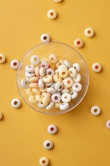 Vista superior de doces redondos coloridos em tigela transparente