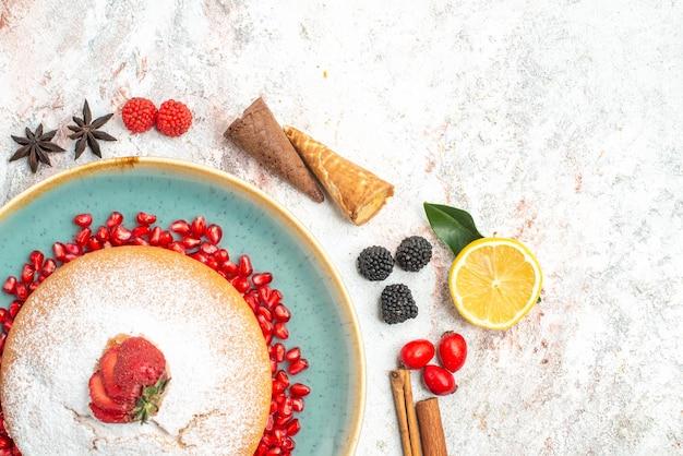 Vista superior de doces, um bolo com anis estrelado de romã, canela, paus, frutas, limões