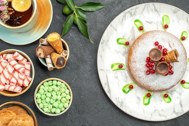Vista superior de doces uma xícara de chá, frutas cítricas, biscoitos, waffles, bolo, doces, frutas