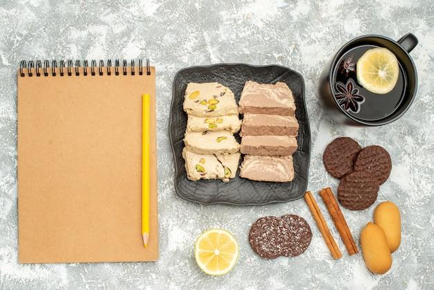 Vista superior de doces uma xícara de chá limão, semente de girassol, halva, biscoitos, creme, caderno, lápis