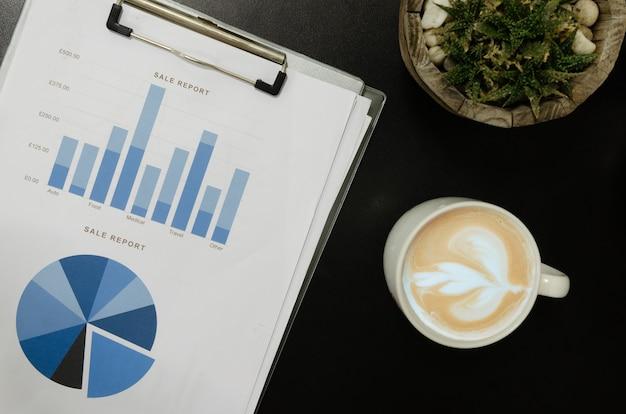 Vista superior de documentos comerciais, gráficos e tabelas e canecas de café. cactus na mesa