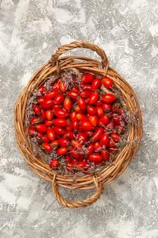 Vista superior de dogwoods azedos frescos dentro de uma cesta na superfície branca fruta baga vitamina azeda planta madura selvagem