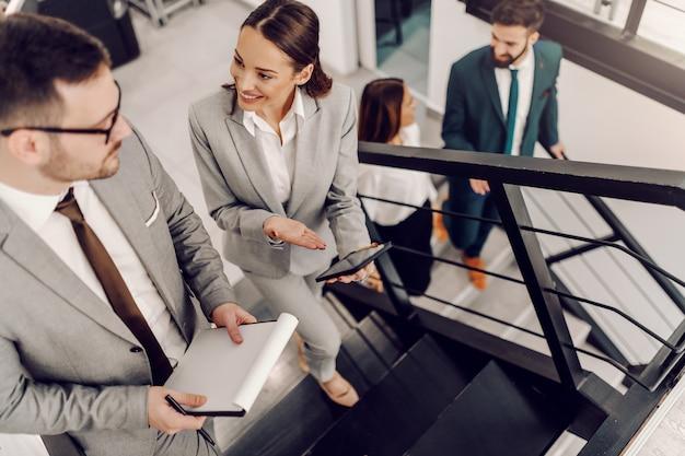 Vista superior de dois colegas felizes com roupa formal, subindo a escada e falando sobre negócios. mulher segurando o tablet enquanto o homem segurando a papelada.