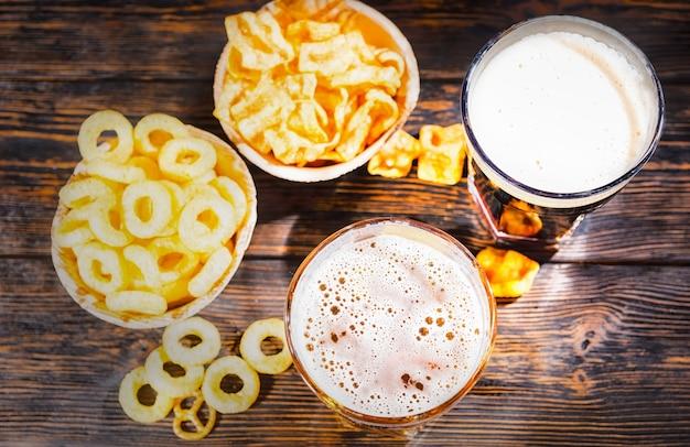 Vista superior de dois copos com cerveja clara e escura recém-derramada perto de pratos com lanche e batatas fritas na mesa de madeira escura. conceito de alimentos e bebidas