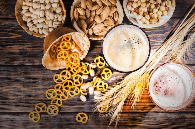 Vista superior de dois copos com cerveja escura e clara recém-derramada perto de trigo, pequenos pretzels e pistache espalhados na mesa de madeira escura. conceito de alimentos e bebidas