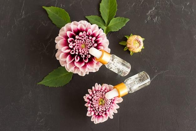 Vista superior de dois frascos de cosméticos transparentes com uma pipeta e flores roxas dália. fundo preto, folhas verdes. conceito de cosméticos naturais.