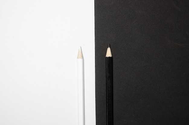 Vista superior de dois lápis de madeira preto e branco em um fundo preto e branco