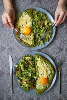 Vista superior de dois pratos com omelete e salada em cima da mesa