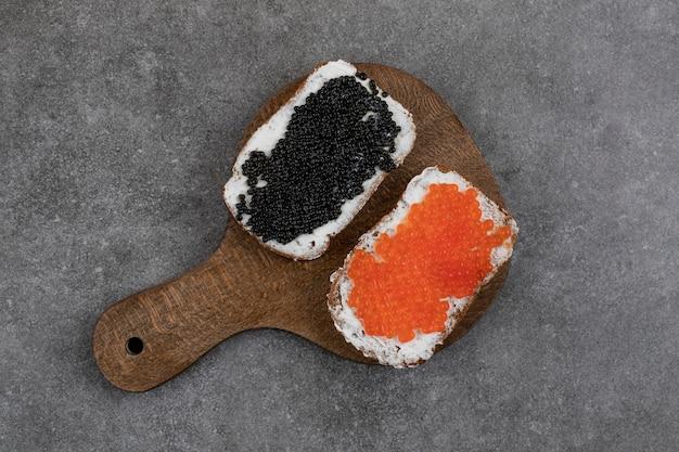 Vista superior de dois sanduíches de caviar fresco na placa de madeira