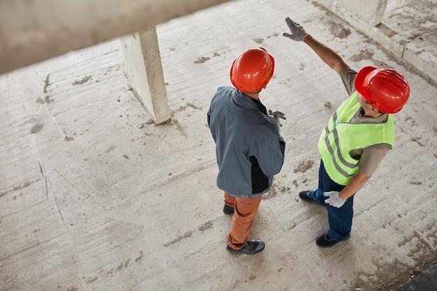 Vista superior de dois trabalhadores da construção civil usando capacetes no espaço da cópia do local da construção