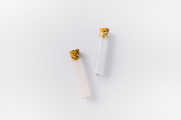 Vista superior de dois tubos de ensaio de óleo essencial na superfície branca