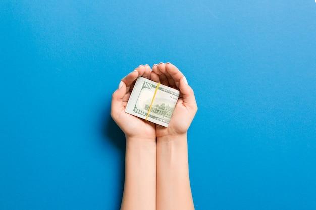 Vista superior de dólares nas palmas das mãos femininas. conceito de pequena pensão