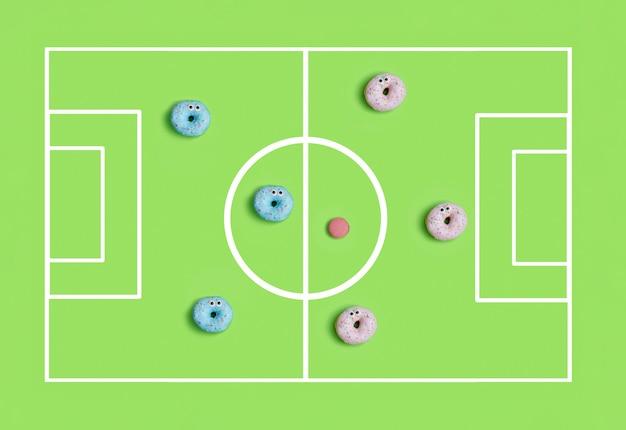 Vista superior de donuts coloridos engraçados jogando futebol, conceito de tempo de festa infantil