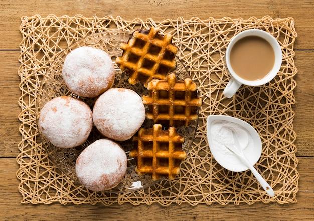 Vista superior de donuts com açúcar em pó e waffles