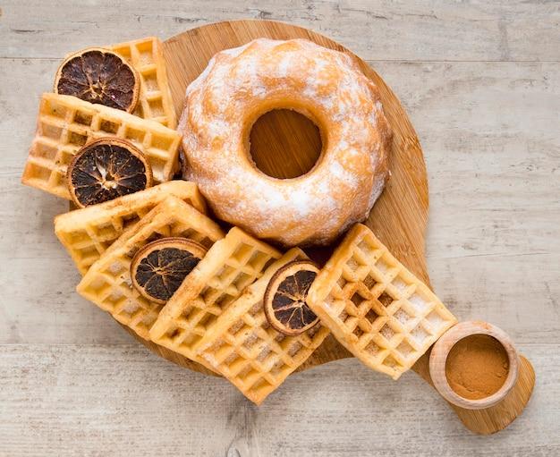 Vista superior de donuts com waffles e frutas cítricas secas
