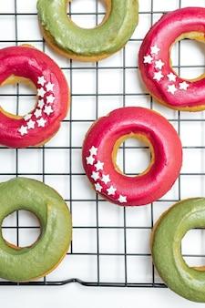 Vista superior de donuts cozidos frescos com glacê rosa e verde brilhante, star granulado na cremalheira de arrefecimento