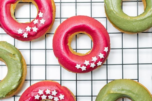 Vista superior de donuts cozidos frescos com glacê rosa e verde brilhante