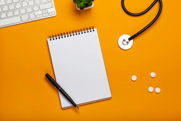 Vista superior, de, doutor, escrivaninha, com, estetoscópio, teclado, notepad, e, caneta, prescrição, e, pílulas