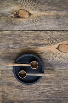 Vista superior de duas colheres de madeira na placa preta na mesa de madeira