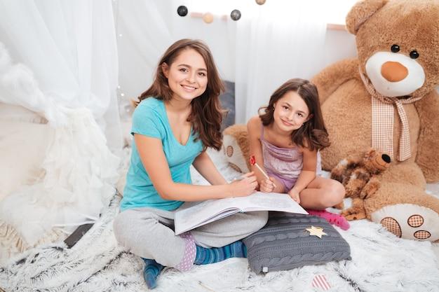 Vista superior de duas irmãs encantadoras e alegres, sentadas e pintando na sala de jogos em casa