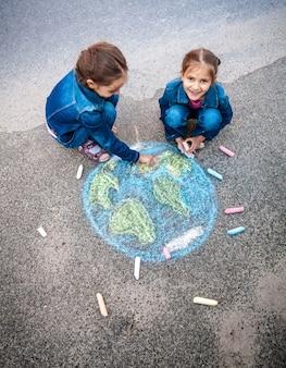 Vista superior de duas meninas desenhando a terra com giz