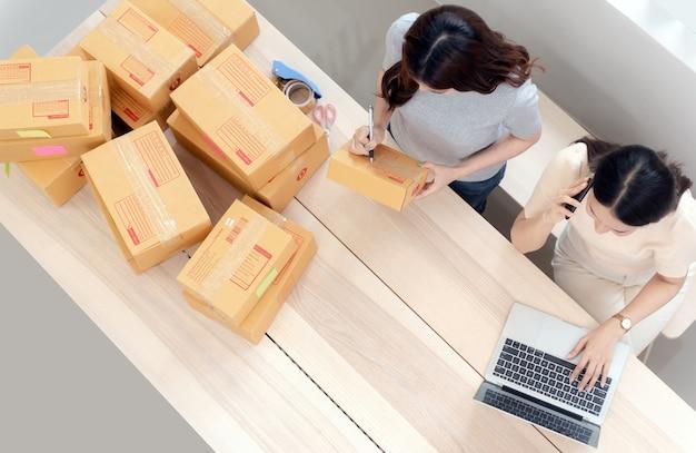 Vista superior de duas mulheres asiáticas vendendo produtos online em casa, com caixas de papel e laptops, sendo um novo negócio online normal