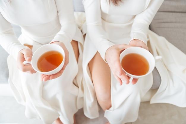 Vista superior de duas mulheres atraentes em vestidos brancos, sentadas e segurando duas xícaras de chá