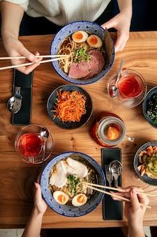 Vista superior de duas pessoas comendo sopas de macarrão ramen japonesas e outros pratos asiáticos