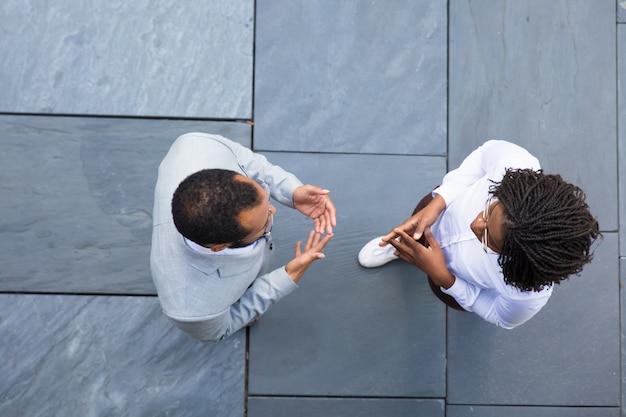 Vista superior de duas pessoas falando de negócios
