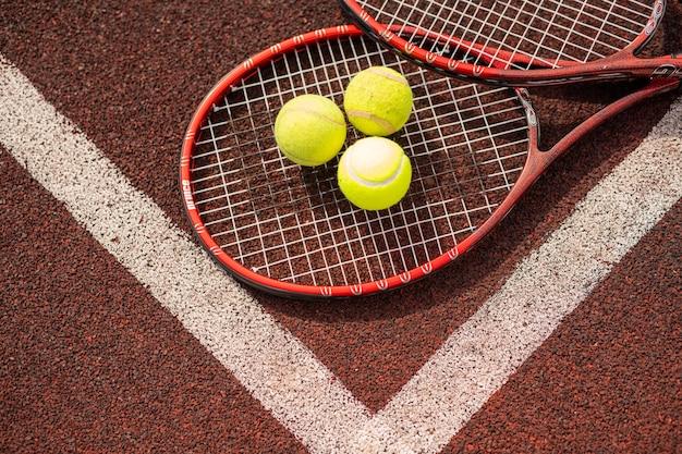 Vista superior de duas raquetes de tênis e três bolas amarelas pelo cruzamento de linhas brancas