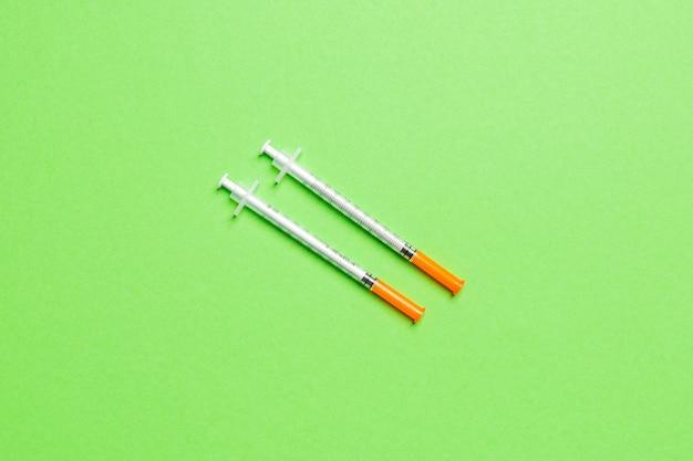 Vista superior de duas seringas de insulina em fundo colorido com espaço de cópia. alto nível de conceito de glicose.