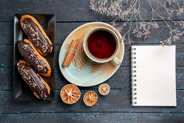 Vista superior de éclairs de chocolate em placa retangular, uma xícara de chá com limão seco e canela e um caderno