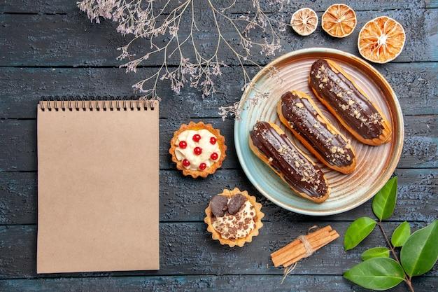 Vista superior de éclairs de chocolate em prato oval tortas de galho de flores secas, folhas de laranjas secas de canela e um caderno na mesa de madeira escura