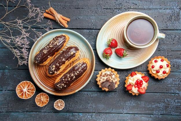 Vista superior de éclairs de chocolate em prato oval, uma xícara de chá, tortas de limão seco e canela na mesa de madeira escura