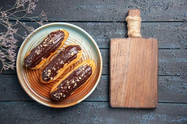 Vista superior de éclairs de chocolate em um galho de flor seca de prato oval e uma tábua de cortar na mesa de madeira escura